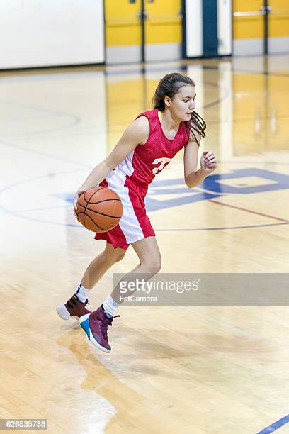 Teenage girl looking intense as she dribbles down court