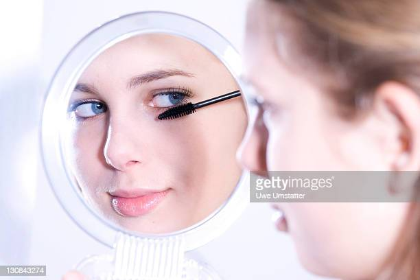 Teenage girl looking into a mirror while applying mascara