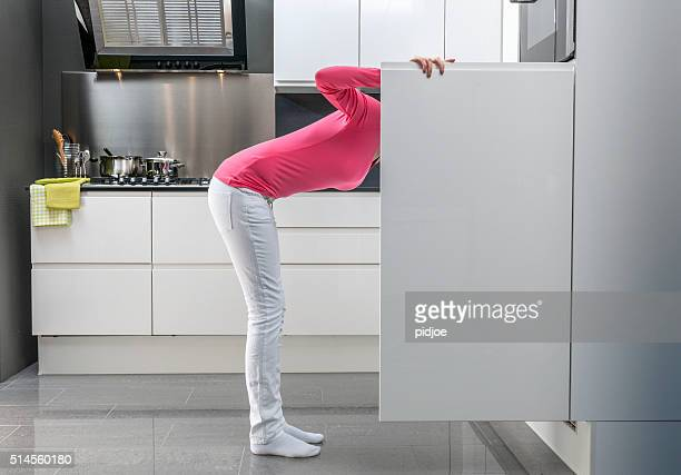 teenage girl looking into refrigerator for a snack