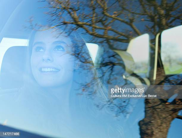 Teenage girl looking out car window