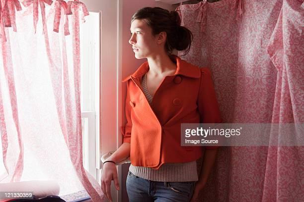 Teenager-Mädchen auf der Suche von Fenster im Badezimmer