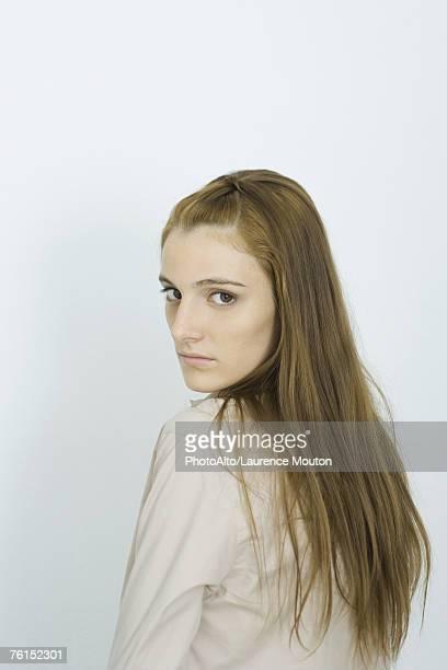 'Teenage girl looking over shoulder at camera, portrait'