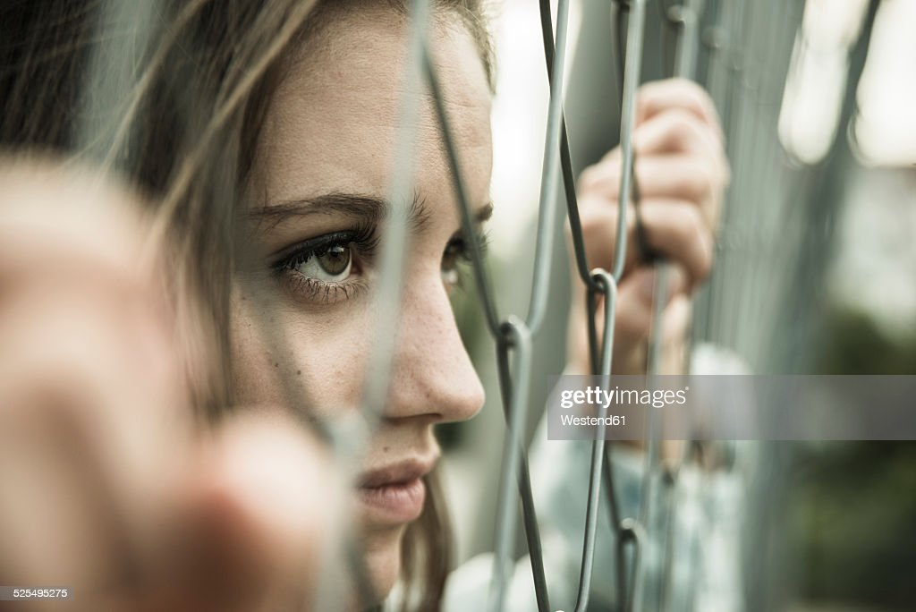 Teenage girl looking through a wire fence