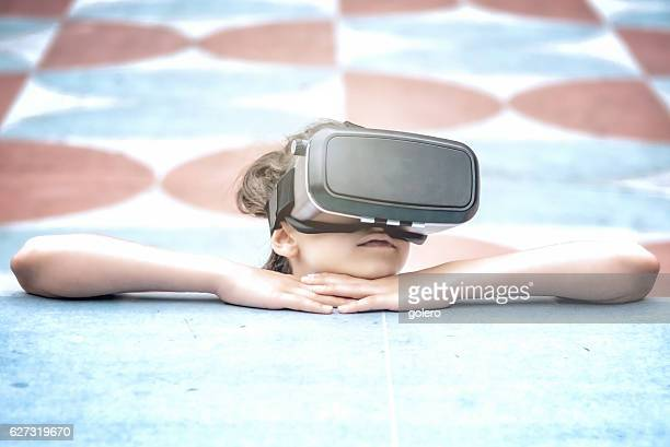 teenage girl looking with black  virtual reality simulator outdoors