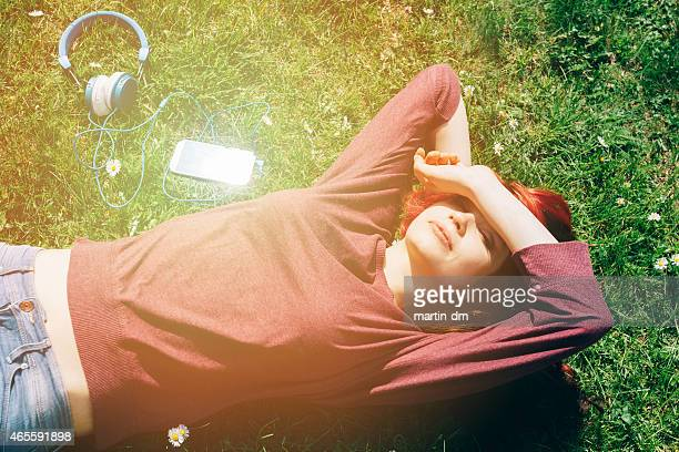 Teenage girl lying down at the grass