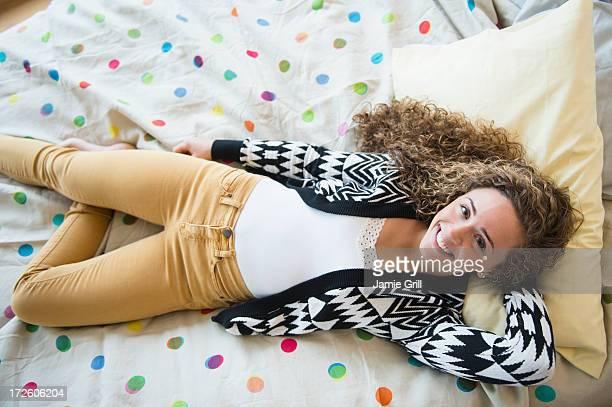 Teenage girl lying in bed, smiling
