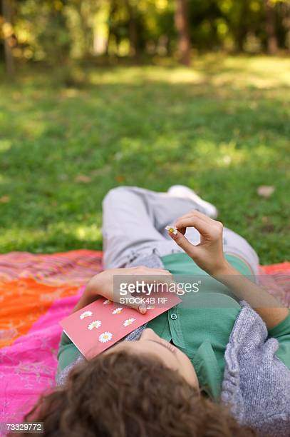 Teenage girl lying on a sheet with a postcard and a daisy in her hand, selective focus
