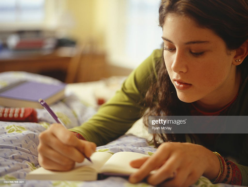 Teenage girl (16-17) lying on bed, writing, close-up : Stock Photo