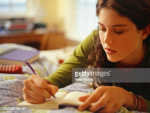 Teenage girl (16-17) lying on bed, writing, close-up : Foto de stock