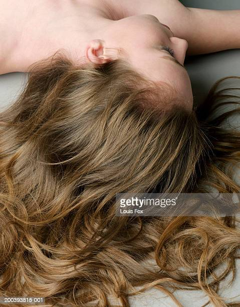 Teenage girl (14-16) lying on floor with hair fanned out