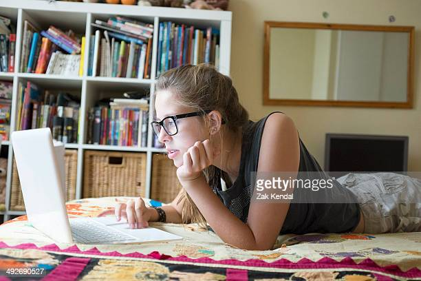 Teenage girl lying on front using laptop