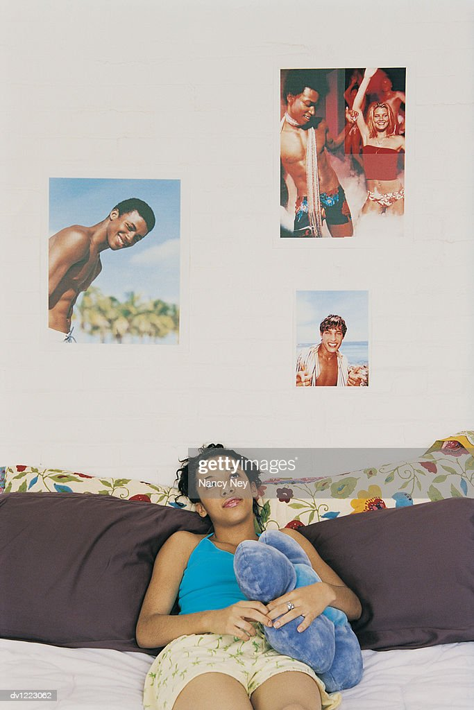 Teenage Girl Lying on Her Bed in a Bedroom Daydreaming : Stock Photo