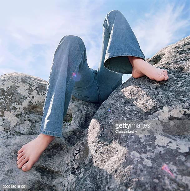 Teenage girl (14-16) lying on rocks, low section