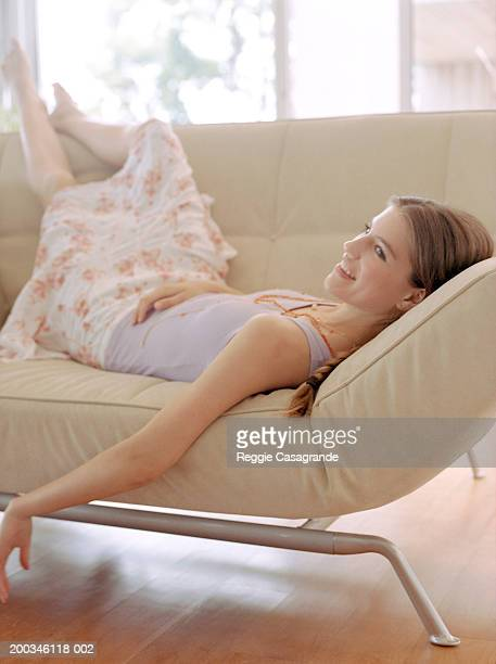 Teenage girl (13-15) lying on sofa