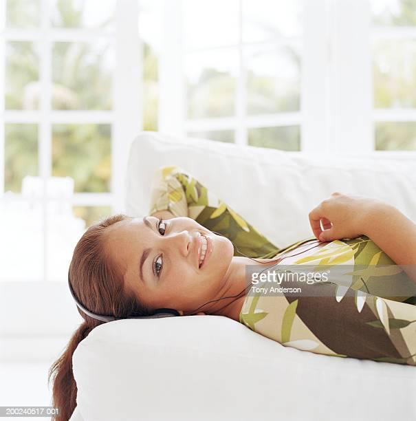 Teenage girl (16-18) lying on sofa, portrait