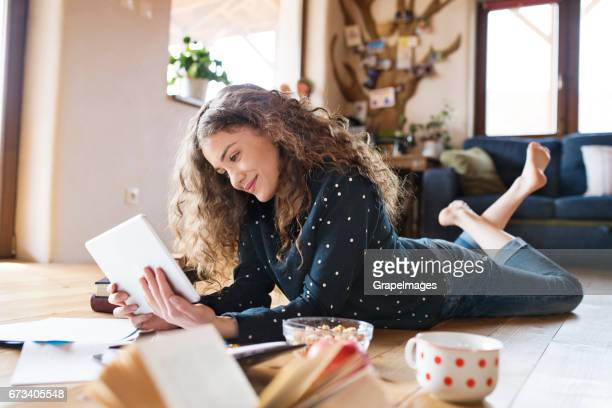 Teenage girl lying on the floor holding tablet, studying