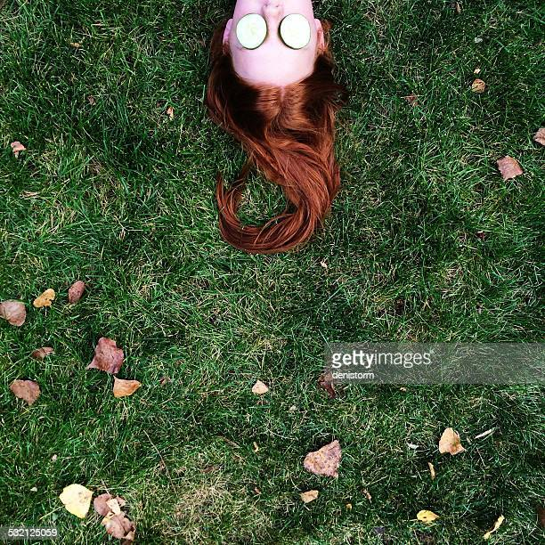 High section shot of redhead teenage girl (14-15) lying on grass, with slices of cucumbers covering her eyes