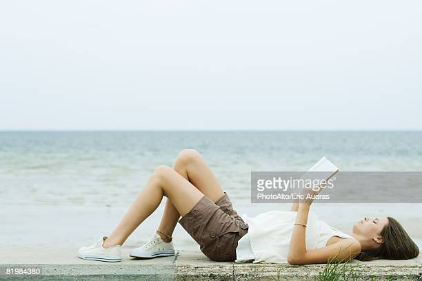 Teenage girl lying on the ground with knees up, reading book, side view