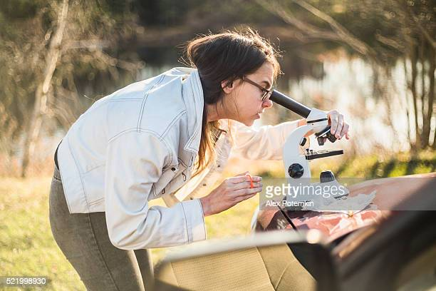 Teenage girl make outdoors scientific project with microscope