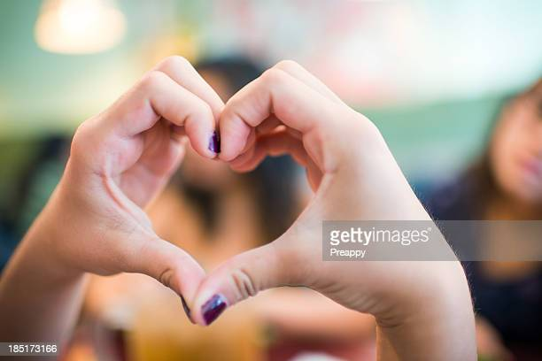 Teenage girl making a heart shape with hands