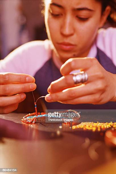 Teenage girl making beaded jewelry