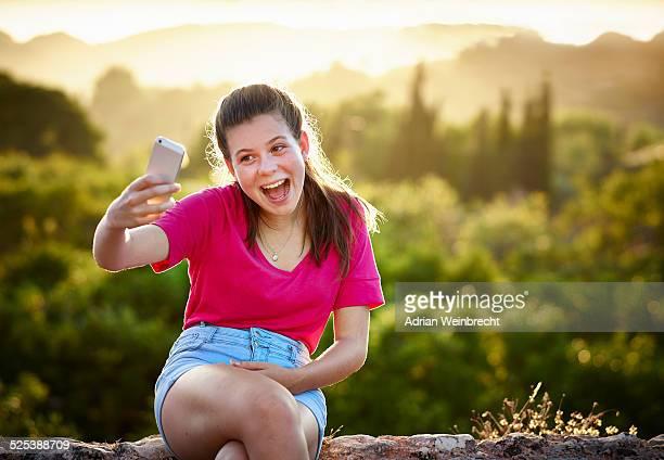 Teenage girl making face for selfie on smartphone, Majorca, Spain
