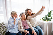 A teenage girl, her mother and grandmother with smartphone at home, taking selfie. Family and generations concept.