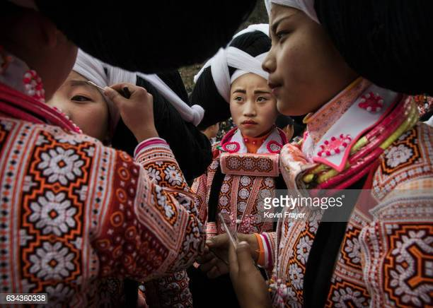 A teenage girl of the Long Horn Miao ethnic minority group has makeup applied as she and others wear headdresses as they prepare to celebrate Tiaohua...
