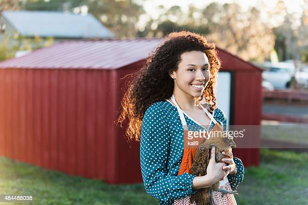 Teenage girl on a farm holding hen