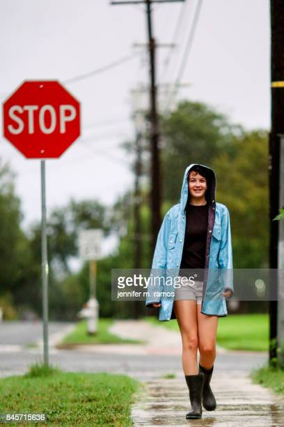 Teenage girl on a sidewalk in the rain wearing a blue raincoat in Austin Texas