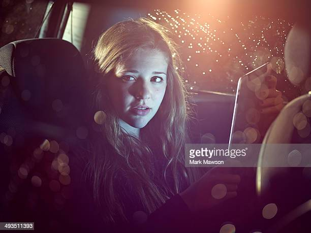 teenage girl on an iPad in a car at night