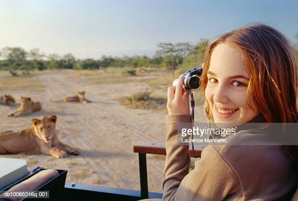 Teenage girl (13-14) on safari in off-road vehicle holding binoculars, lionesses sitting in bush in background