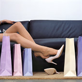 Teenage girl on sofa kicking off shoes by shopping bags, low section