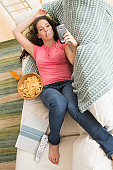 Teenage girl on texting on couch with junk food