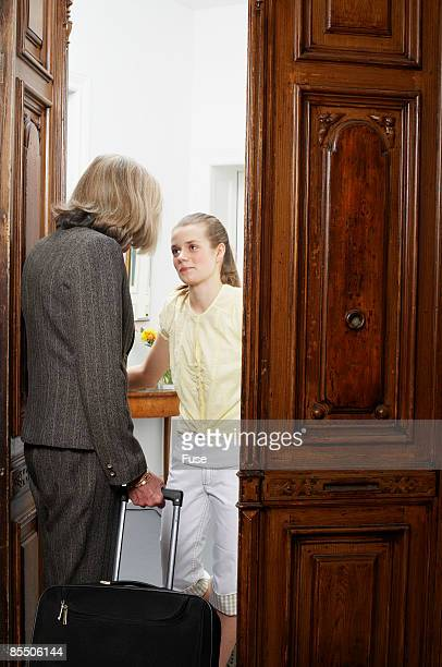 Teenage Girl Opening Door for Senior Woman