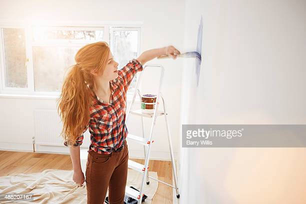 Teenage girl painting her bedroom wall