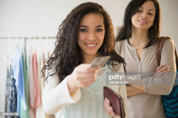 Teenage girl paying with credit card in store