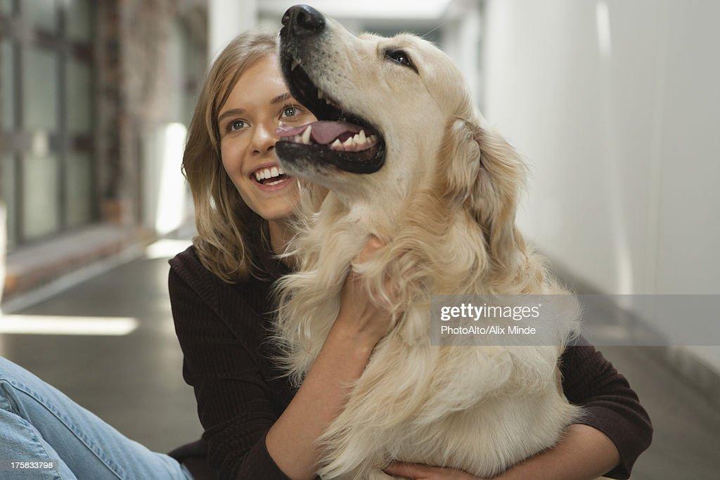 Teenage girl petting golden retriever : Stock Photo