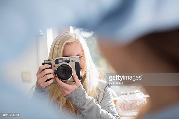 Teenage girl photographing friend with camera