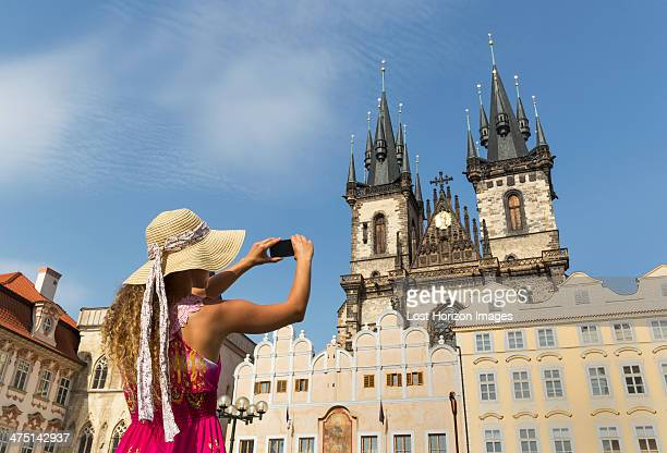 Teenage girl photographing Our Lady of Tyn church, Prague, Czech Republic