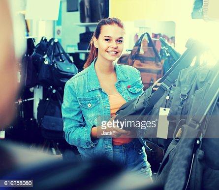 teenage girl picking  handbag : Foto de stock
