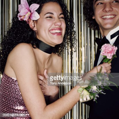 Teenage girl (16-18) pinning boutonniere on date, laughing, close up : Stock Photo