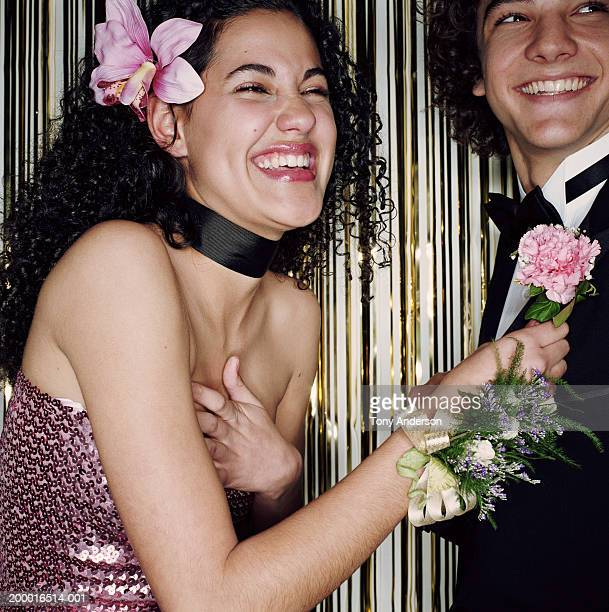 Teenage girl (16-18) pinning boutonniere on date, laughing, close up