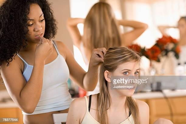 Teenage girl pinning friend's hair