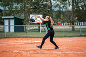 A teenage girl in fast ball pitching stance on the pitchers mound in black and green uniform