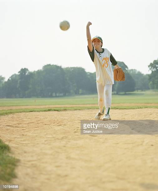Teenage girl (12-14) pitching softball