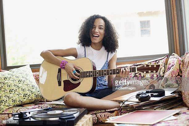 Teenage girl playing acoustic guitar and singing indoors