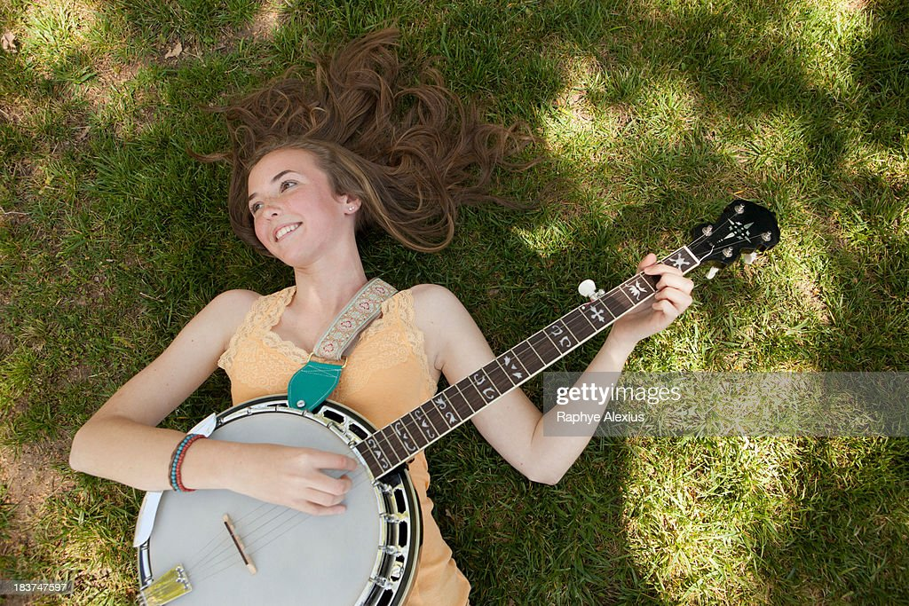 Teenage girl playing banjo on grass, overhead view