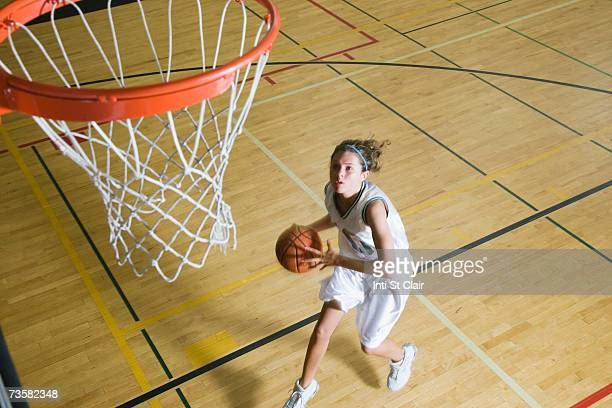 Teenage girl (16-18) playing basketball, elevated view