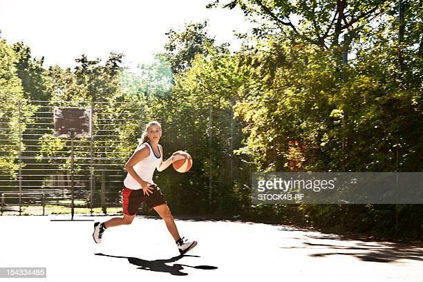 Teenage girl playing basketball